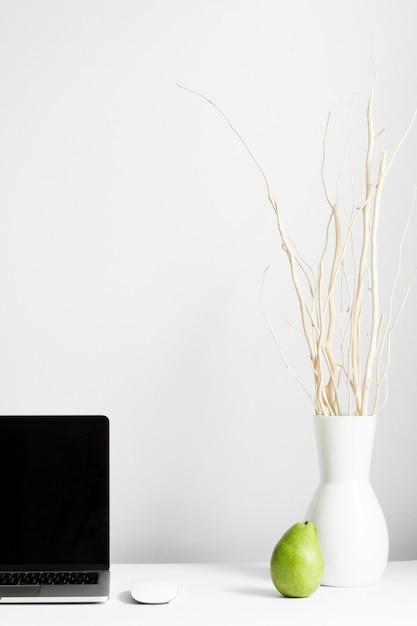 Composition du lieu de travail avec vase et ordinateur portable sur le bureau Photo gratuit