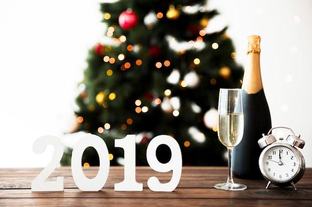 Composition du nouvel an avec une bouteille de champagne et une horloge sur une table Photo gratuit