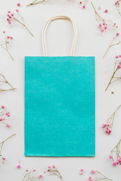 Composition avec emballage bleu et fleurs roses Photo gratuit