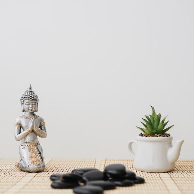 Composition avec la figure de bouddha et le pot Photo gratuit