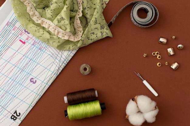 Composition avec fils à coudre et accessoires sur fond blanc, vue de dessus Photo Premium