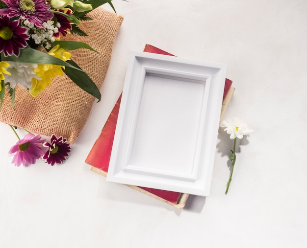 Composition de fleurs et cadre photo sur un bureau gris Photo gratuit