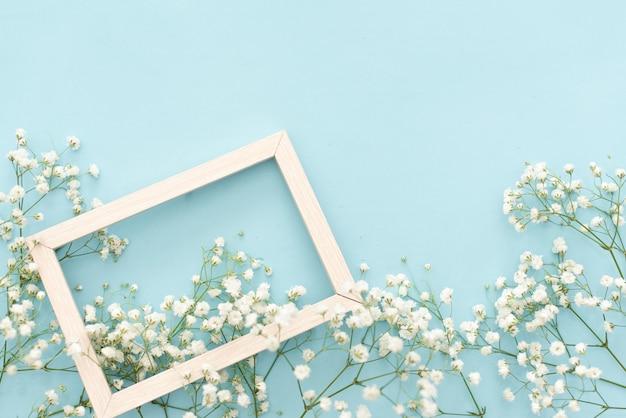 Composition de fleurs romantique. fleurs de gypsophile blanc, cadre photo sur fond bleu pastel. Photo Premium