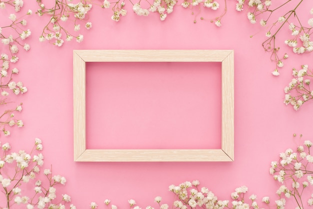Composition de fleurs romantique. fleurs de gypsophile blanche, cadre photo sur fond rose pastel. Photo Premium
