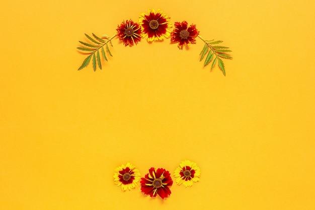 Composition florale. couronne florale ronde de fleurs jaunes rouges sur fond orange Photo Premium