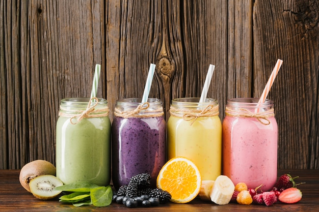 Composition de fruits et smoothies colorés sur fond en bois Photo gratuit