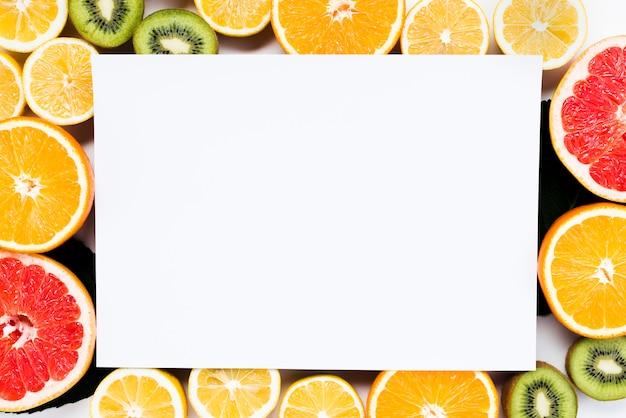 Composition de fruits tropicaux colorés tranchés avec un morceau de papier blanc Photo gratuit