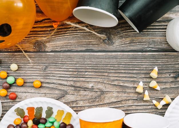 Composition avec des gobelets en papier épars et des bonbons sur une table en bois Photo gratuit