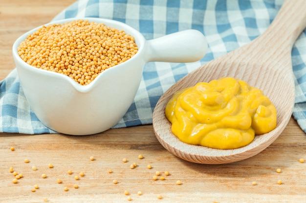 Composition de graines de moutarde et de moutarde sur fond de bois. Photo Premium