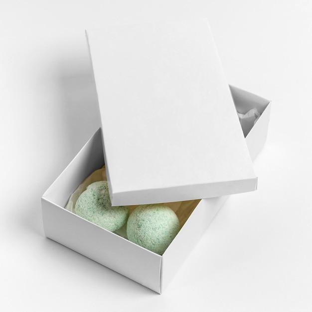 Composition De Grand Angle De Bombes De Bain Vert En Boîte Sur Fond Blanc Photo gratuit