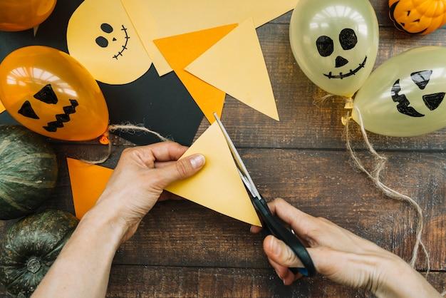 Composition d'halloween avec les mains coupant le papier Photo gratuit