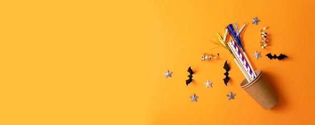 Composition de halloween de verres en papier, tubes multicolores pour boissons, chauves-souris en papier noir, étoiles Photo Premium