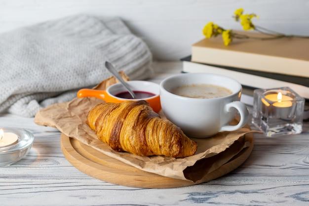 Composition Hygge Confortable Avec Un Croissant Fait Maison Frais Et Du Café Sur Une Table En Bois Avec Des Bougies, Des Livres Et Des Tricots Photo Premium