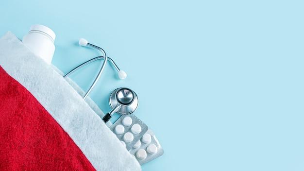 Composition Médicale De Noël Avec Pilules, Pot De Vitamines Et Stéthoscope Au Chapeau Rouge Du Père Noël Photo Premium