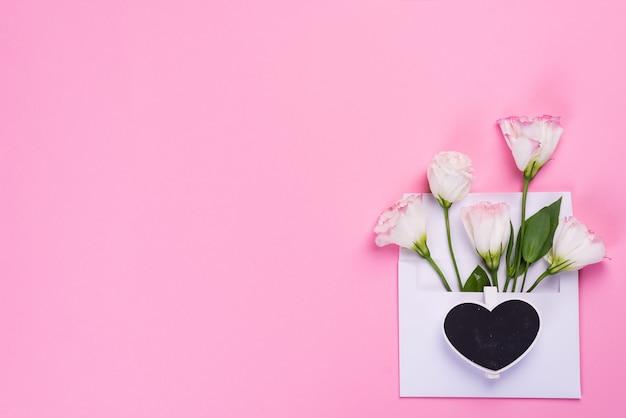 Composition Minimale Avec Un Eustoma En Fleurs Dans Une Enveloppe Avec Un Tableau Noir En Forme De Coeur Sur Fond Rose, Vue De Dessus. Carte De Voeux Saint Valentin Photo Premium