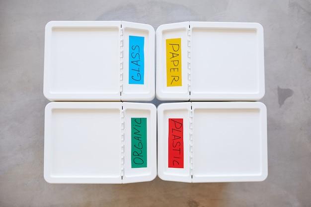 Composition Minimale De La Vue De Dessus De Quatre Bacs En Plastique étiquetés Pour Le Stockage Et Le Tri Des Déchets à La Maison Photo Premium