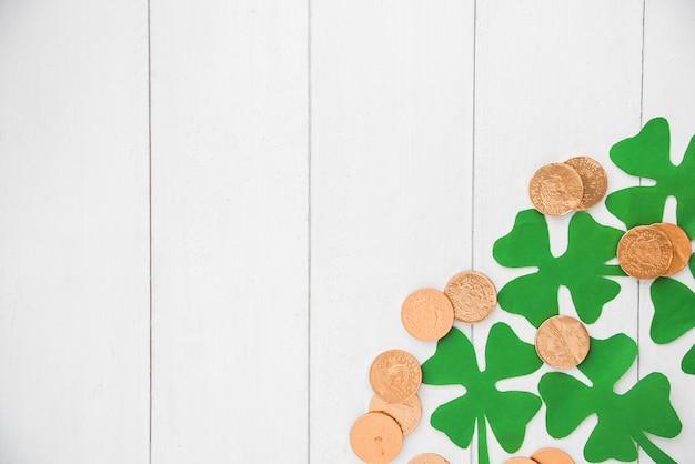 Composition de monnaies et de trèfles verts à bord Photo gratuit