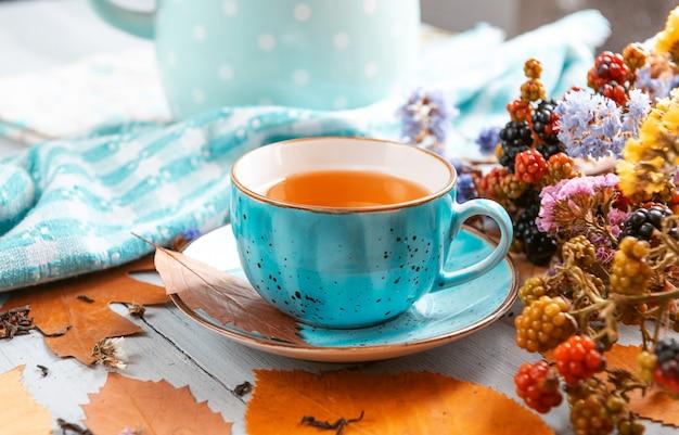 Composition nature morte d'un mug avec du thé en feuilles avec des baies et des feuilles d'automne sur une surface en bois Photo Premium