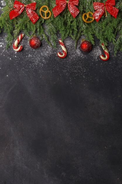 Composition de noël de branches de conifères, de décorations et de sucreries sur fond sombre. lay plat. vue de dessus nature nouvel an concept. espace de copie. Photo Premium