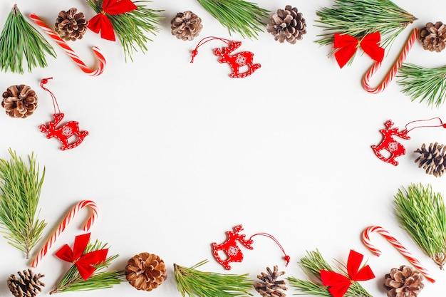 Composition De Noël. Branches De Sapin, Jouets De Noël En Bois Rouge, Arcs, Cannes De Bonbon Sur Fond Blanc. Photo Premium