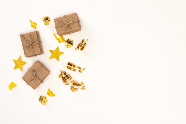 Composition de noël cadeau, décorations de noël dorées, branches de cyprès, pommes de pin. lay plat, vue de dessus Photo Premium