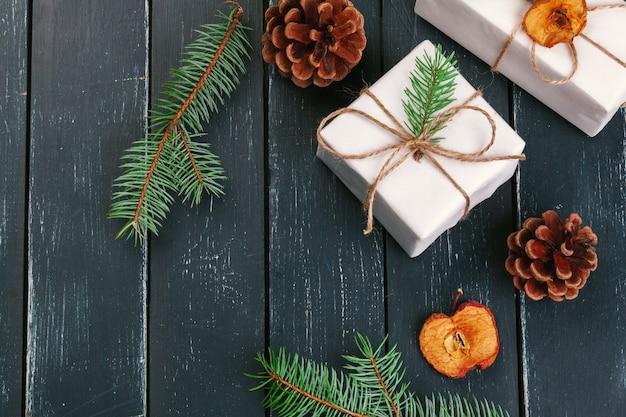Composition De Noël. Cadeau De Noël, Couverture Tricotée, Pommes De Pin, Branches De Sapin Sur Table En Bois. Photo Premium