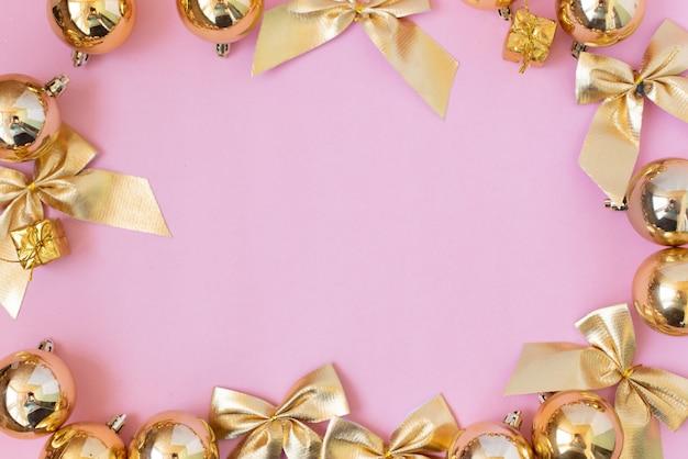 Composition de noël cadeaux de noël, décorations dorées sur rose pastel Photo Premium