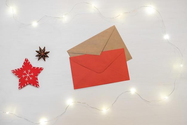 Composition de noël décorations rouges avec enveloppe de lettre sur fond blanc. Photo Premium