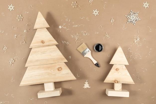 Composition De Noël Ou Du Nouvel An. Arbres De Noël En Bois Faits à La Main, Peinture, Pinceaux Sur Fond Beige Artisanal. Photo Premium