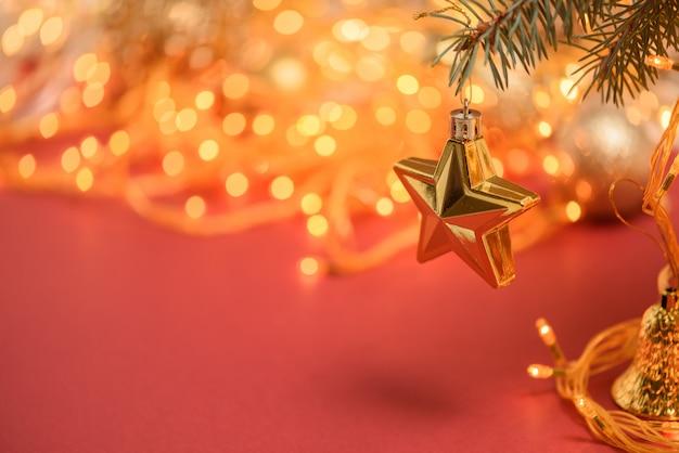 Composition De Noël Etoile Dorée Suspendue à Une Branche D'épinette Sur Fond Rouge Photo Premium