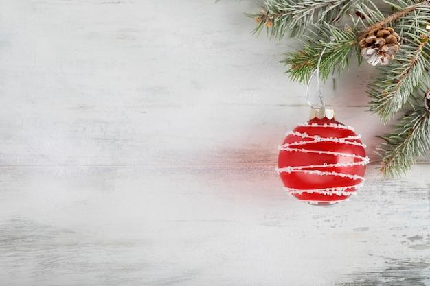 Composition De Noël Sur Un Fond En Bois Clair Recouvert De Neige Blanche. Décoration De Vacances De Noël Avec Boule Rouge. Vue De Dessus. Copyspace Photo Premium