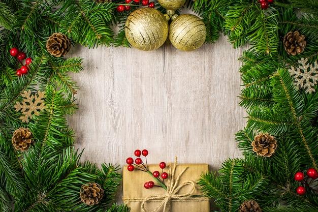 Composition De Noël Sur Fond De Bois Pour Vos Salutations De Vacances D'hiver. Cadeaux De Noël, Pommes De Pin, Gui, Flocons De Neige Sur Un Fond Sombre Texturé. Photo Premium