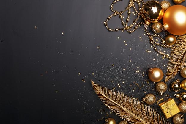 Composition De Noël De Jouets De Noël Doré Et éléments De Décoration Sur Fond Noir. Photo Premium