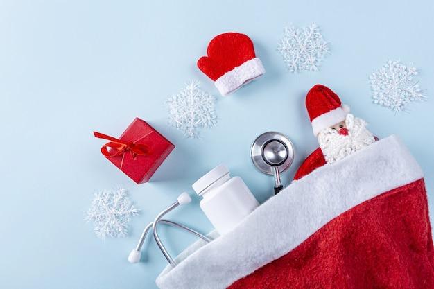 Composition De Nouvel An Médical à Plat Avec Stéthoscope, Pilules, Boîte-cadeau Et Décoration De Noël Photo Premium