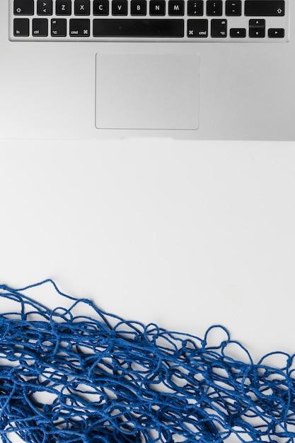 Composition d'ordinateur portable et de résille bleue Photo gratuit