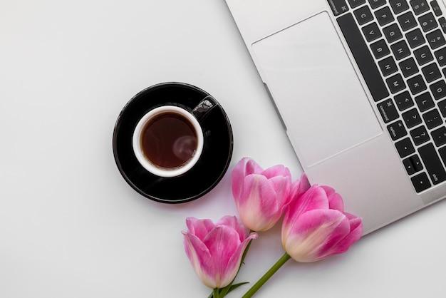 Composition d'un ordinateur portable avec des tulipes et une tasse de café Photo gratuit