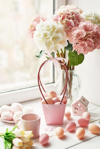 Composition De Pâques Avec Des Hortensias Roses Et Blancs Dans Un Vase, Des Tulipes Jaunes Et Des œufs Roses Photo Premium