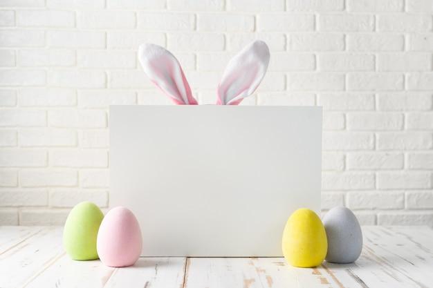 Composition de pâques avec des oeufs, tableau blanc et oreilles de lapin Photo Premium