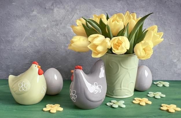 Composition de pâques avec des tulipes jaunes et des poules en céramique avec des oeufs de pâques en vert, jaune et gris Photo Premium