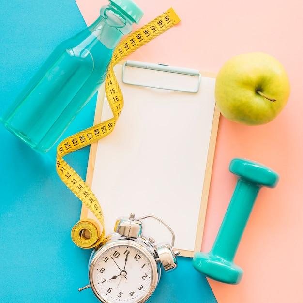 Composition de perte de poids avec presse-papiers, ruban à mesurer et bouteille Photo gratuit