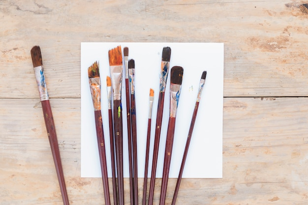 Composition de pinceaux usagés sur papier blanc Photo gratuit