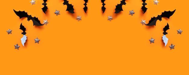 Composition à plat d'halloween de chauves-souris en papier noir et étoiles dorées Photo Premium