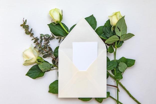Composition Plate Avec Une Enveloppe Blanche, Une Carte Vierge Et Une Fleur Rose. Maquette Pour Mariage Ou Note De Saint Valentin. Vue De Dessus. Photo Premium