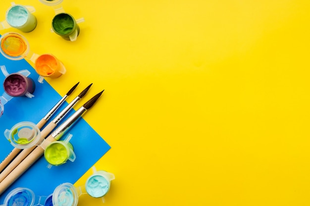 Composition Plate Poser Avec Différentes Peintures à L'acrylique Ou à L'huile Et Des Pinceaux Sur Fond Grunge. Photo Premium