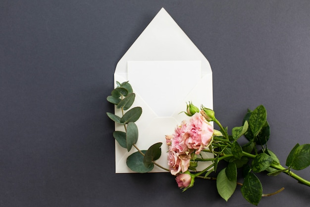 Composition plate poser avec une enveloppe blanche, une carte vierge et une fleur de pivoine rose sur fond gris. maquette pour mariage ou saint valentin. vue de dessus. Photo Premium