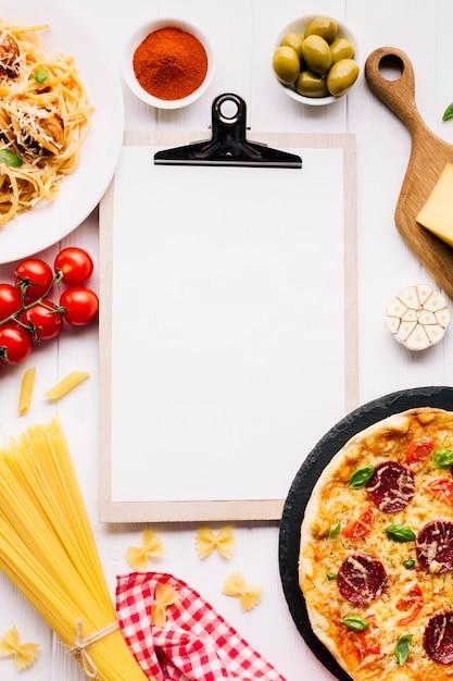 Composition de plats italiens plats laïcs avec modèle de presse-papiers Photo gratuit