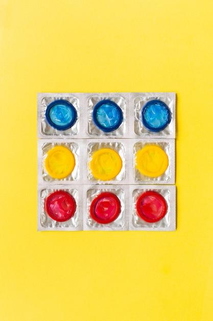 Composition Avec Des Préservatifs Colorés Sur Fond Jaune. Sexe Sans Risque Et Concept Contraceptif. Mise à Plat, Vue De Dessus, Espace De Copie. Photo Premium