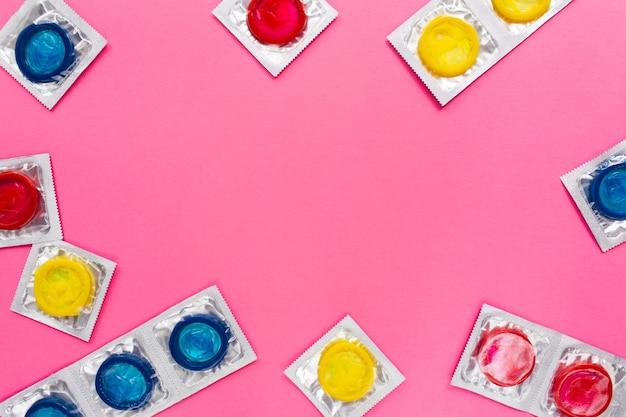 Composition Avec Des Préservatifs Colorés Sur Une Surface Rose Vif Photo Premium