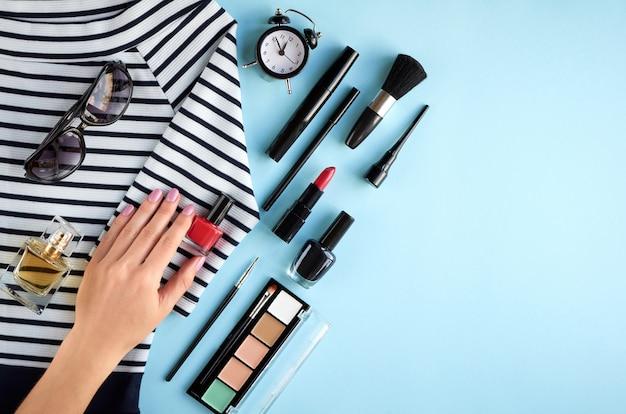 Composition de produits de maquillage différents avec la main sur fond bleu Photo Premium