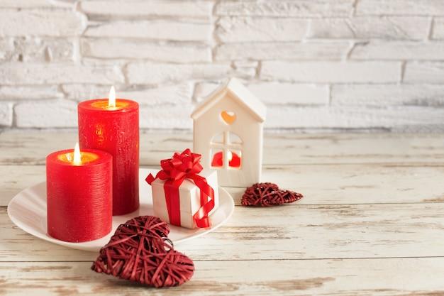Composition Romantique Pour La Saint-valentin Avec Des Bougies Et Des Coeurs Sur Une Table En Bois Sur Le Mur De Briques Blanches. Photo Premium